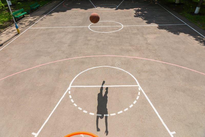 Sombra do homem novo que faz o tiro na rede do basquetebol fotos de stock royalty free