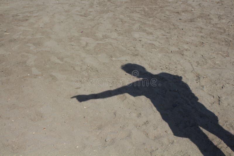 Sombra do homem que aponta no fundo da areia fotografia de stock royalty free