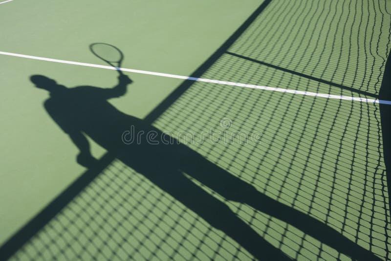 Sombra do homem superior que joga o tênis na corte fotografia de stock