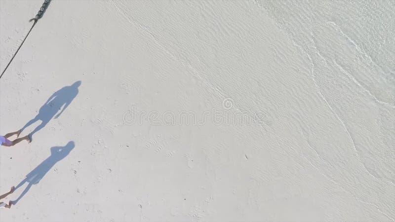 Sombra dos pares na praia Sombra longa de pares novos na areia da praia Sombras doces recentemente de um par do casamento durante imagens de stock royalty free