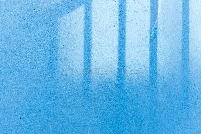 Sombra en fondo azul de la pared fotos de archivo