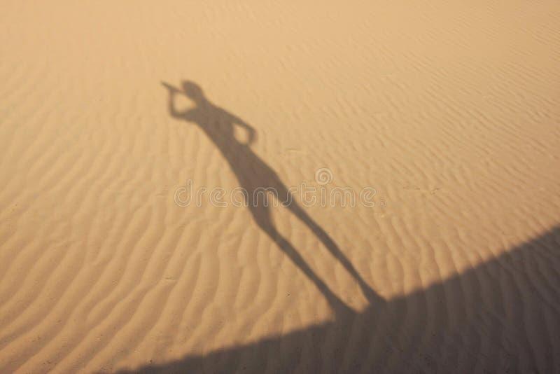 Sombra en las dunas que beben al hombre imagen de archivo