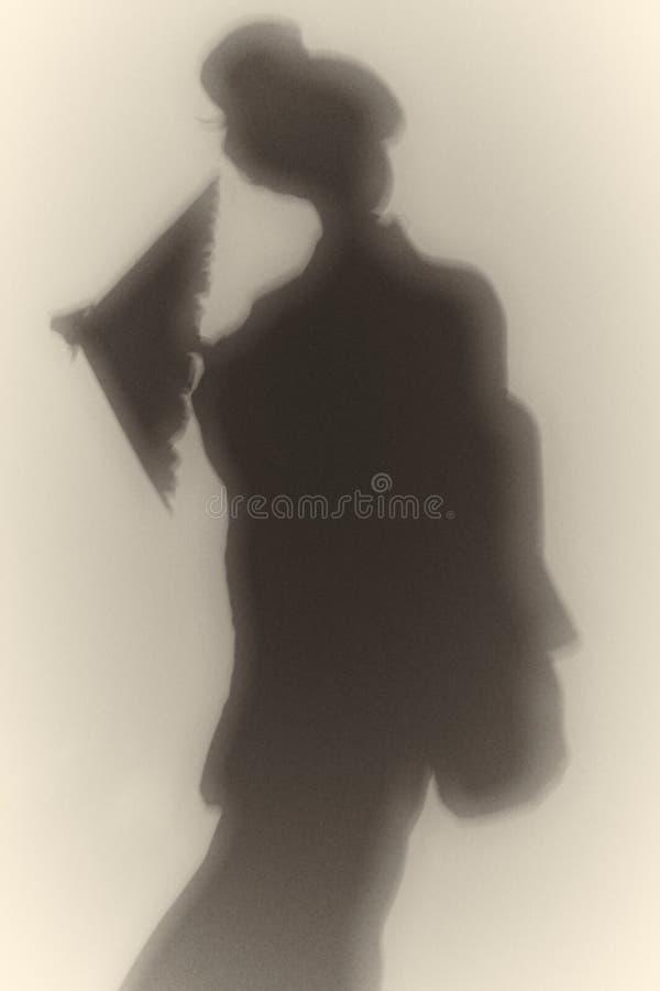 Sombra escura de uma menina de gueixa japonesa em um quimono e com um close-up do guarda-chuva em um fundo branco imagens de stock