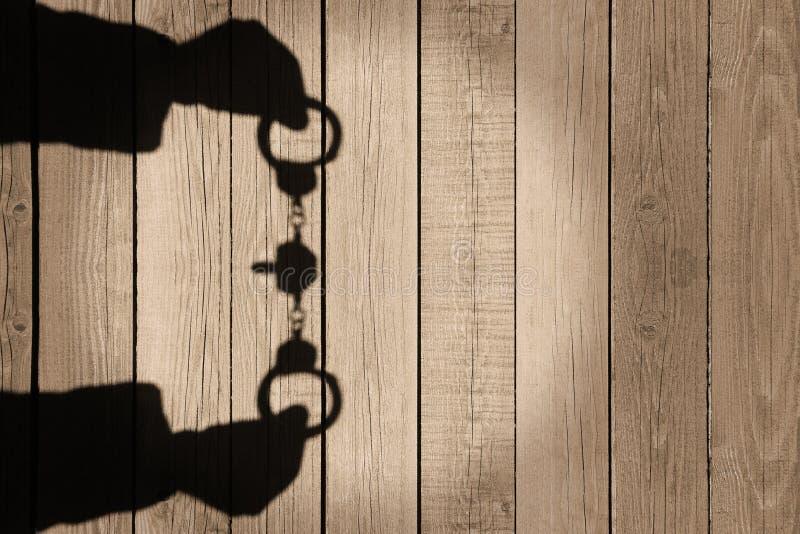 Sombra humana de las manos con las esposas en Backround de madera natural, X foto de archivo libre de regalías