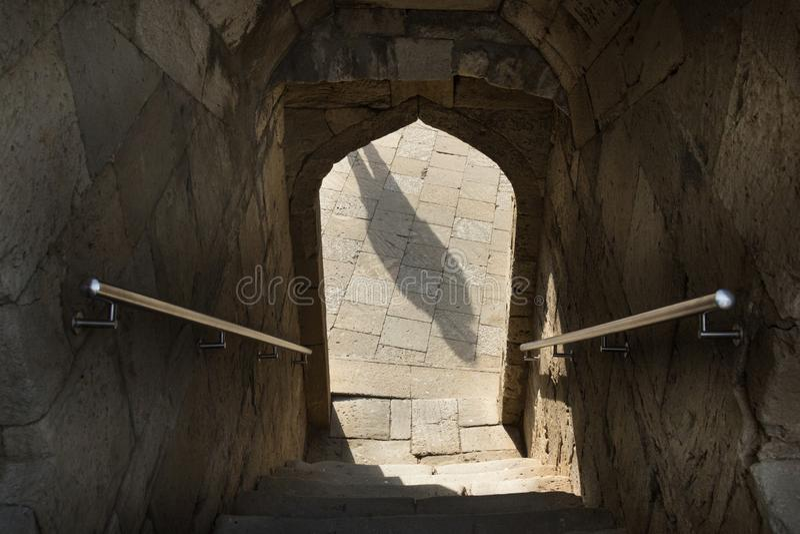 Sombra na entrada do arco, trilhos, escadas abaixo da entrada através do arco foto de stock royalty free