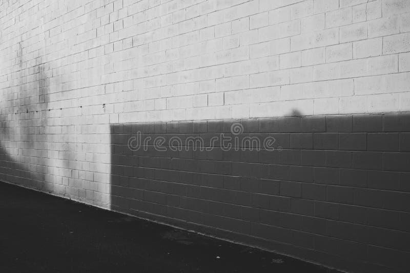 Sombra preto e branco na textura e no asfalto da parede fotografia de stock royalty free