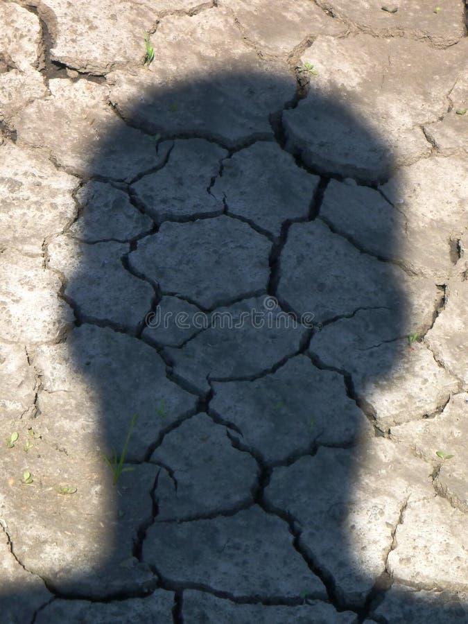 A sombra principal do homem na terra seca imagem de stock
