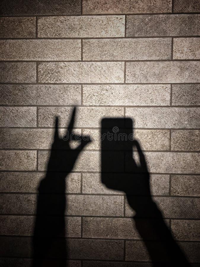 Sombra y sombra de la mano en la pared imagenes de archivo