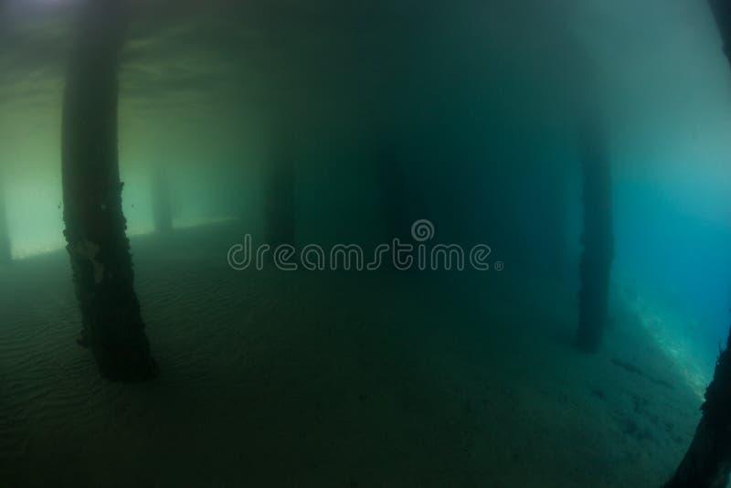 Sombras abaixo de um molhe escuro em Indonésia fotos de stock royalty free