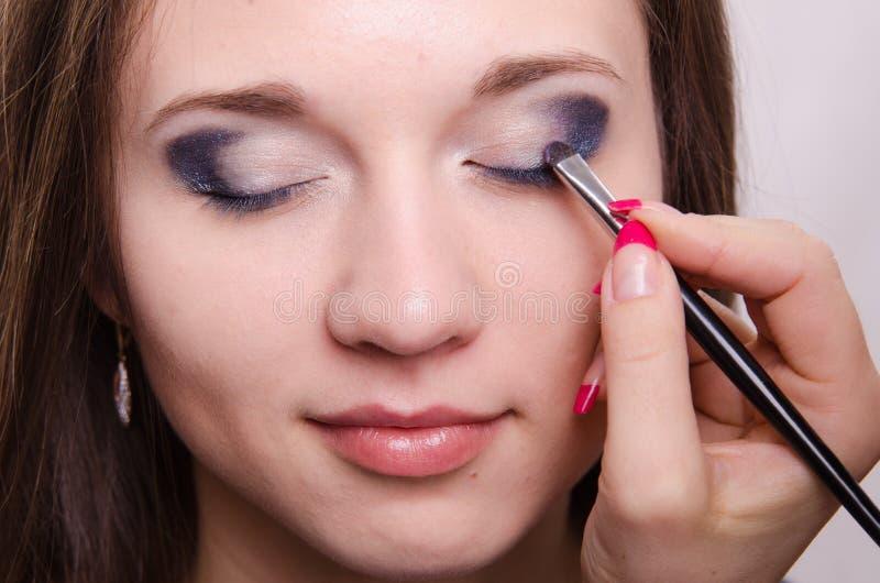 Sombras brillantes de dibujo en los párpados de la muchacha con maquillaje imagen de archivo
