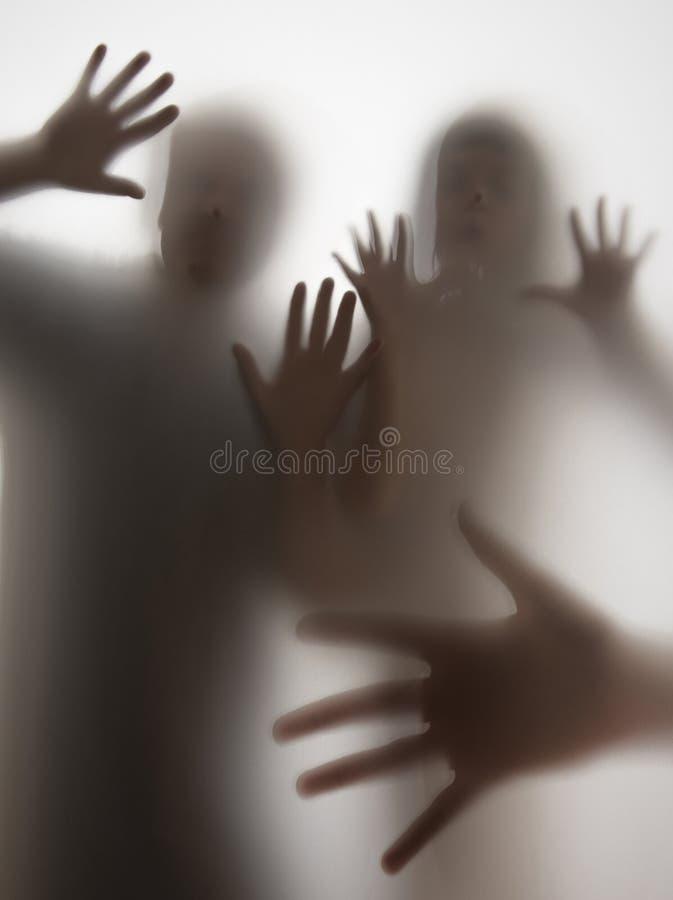 Sombras de la gente detrás del papel transparente foto de archivo libre de regalías