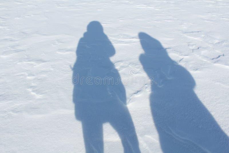 Sombras de la gente en la nieve imagenes de archivo