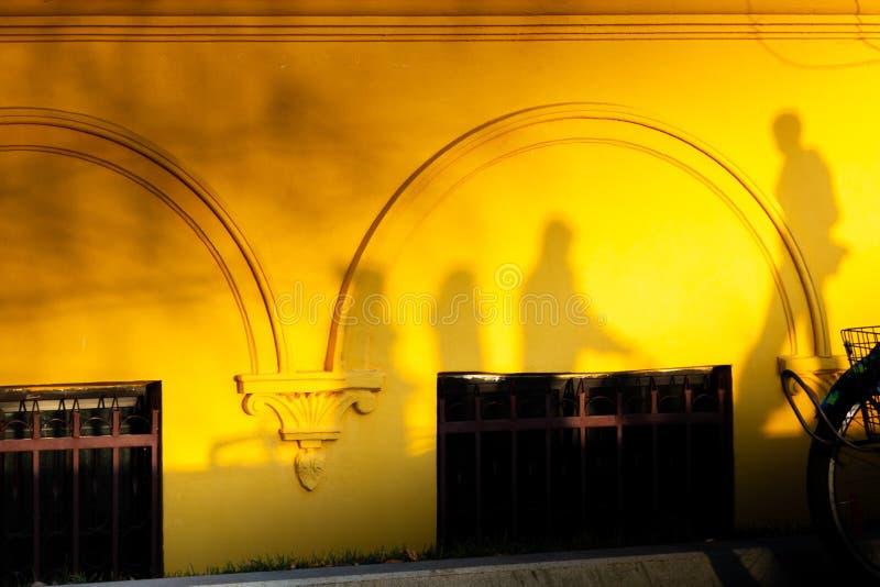 Sombras de la gente en la pared amarilla Madre con el cochecito, niños imágenes de archivo libres de regalías