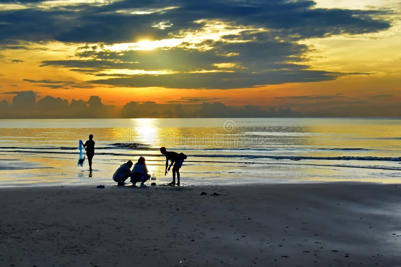 Sombras de la gente que pesca en la playa en la salida del sol fotos de archivo