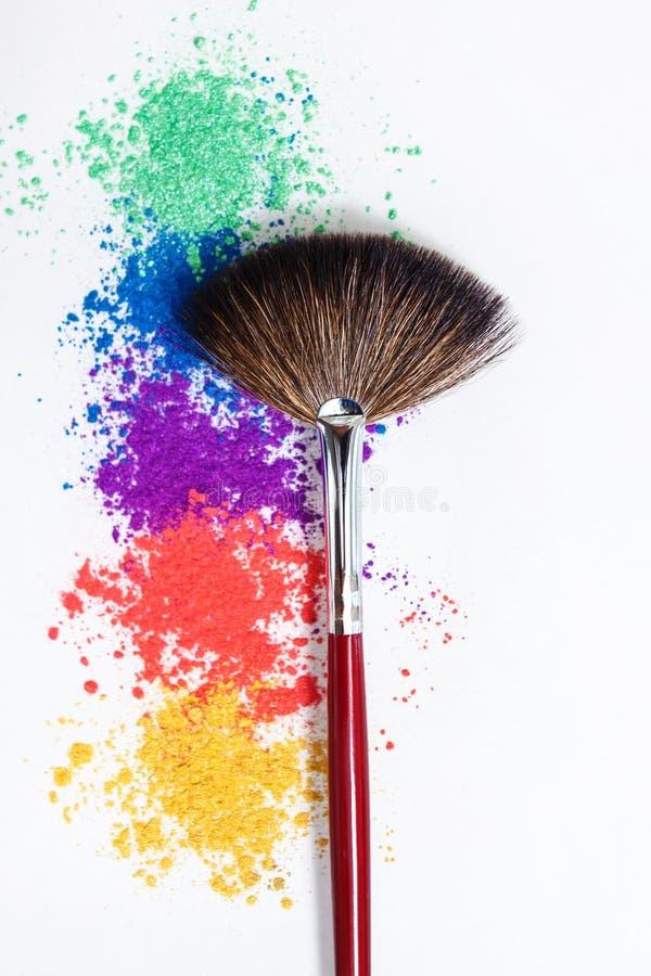 Sombras de ojos brillantes en diversos colores del arco iris y de los cepillos para los cosm?ticos en un fondo blanco foto de archivo