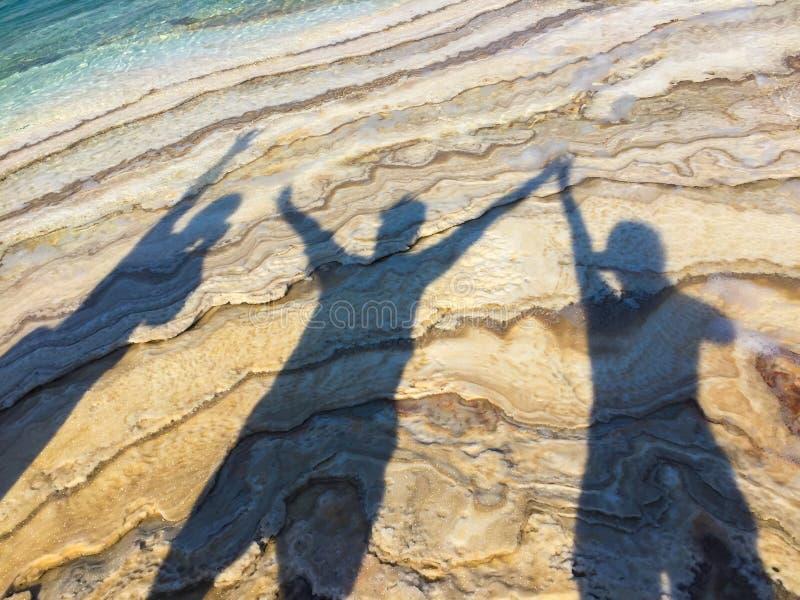 Sombras de tres personas felices en la playa que aumenta las manos imagen de archivo