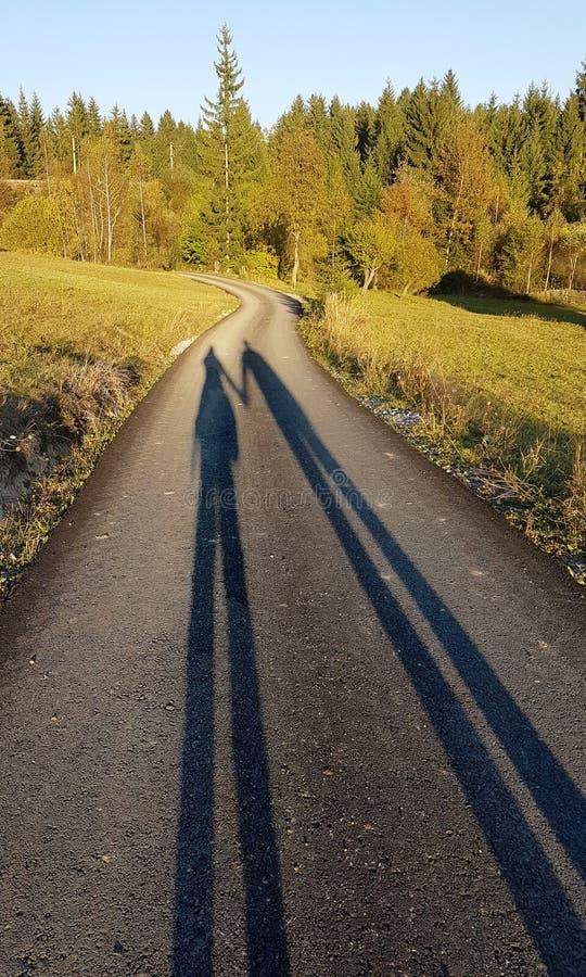 Sombras de um par em uma estrada secundária fotos de stock royalty free