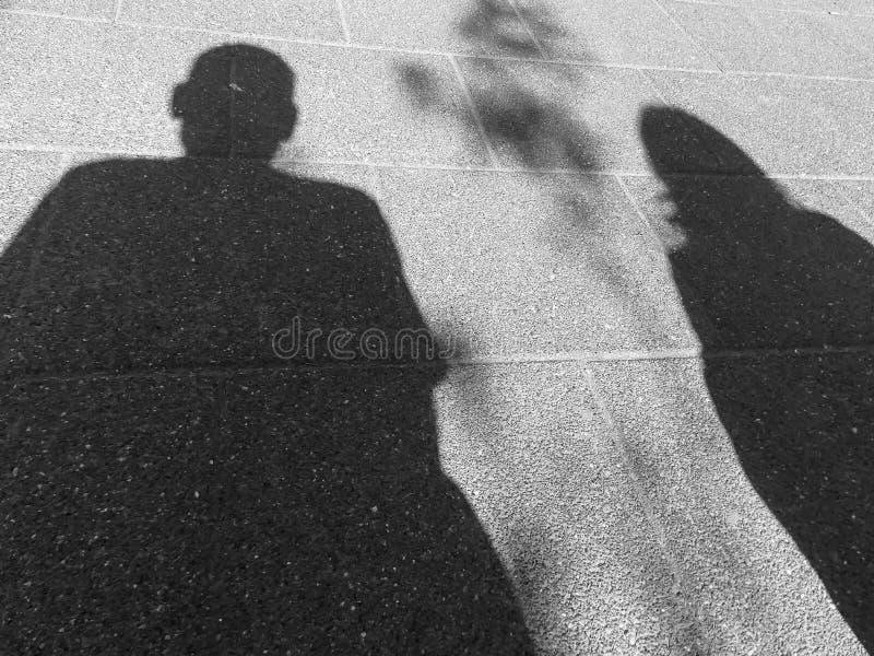 Sombras de un par distante en blanco y negro imagen de archivo