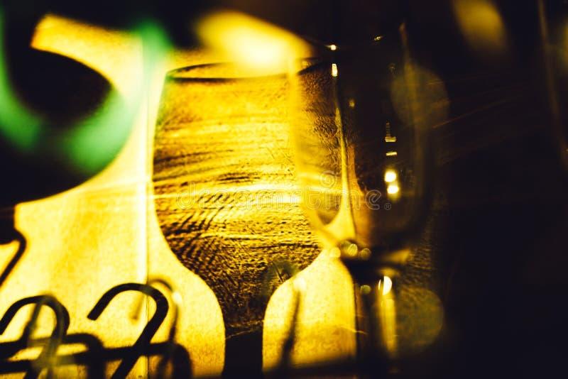 Sombras de vidros de vinho na parede nos raios do sol de ajuste foto de stock