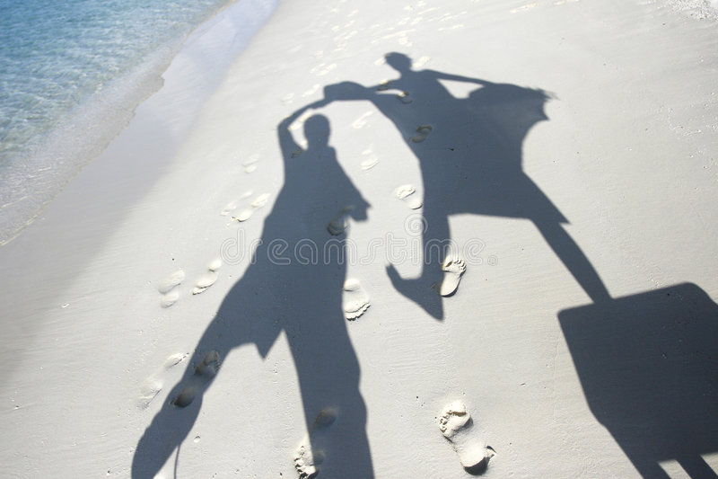 Sombras del baile en las arenas de la playa imágenes de archivo libres de regalías