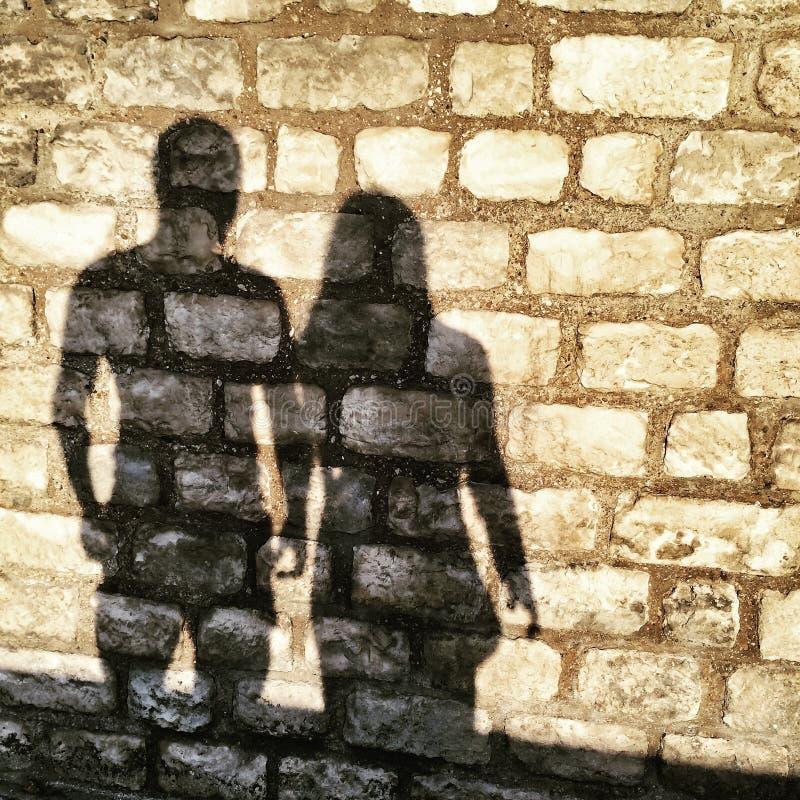 Sombras del hombre y de la mujer en una pared de ladrillo imágenes de archivo libres de regalías