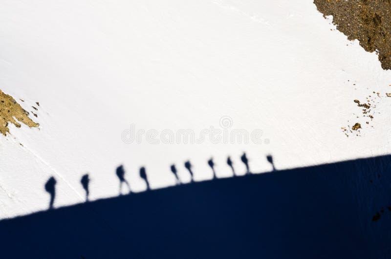 Sombras do grupo de trekkers da montanha em uma neve fotos de stock
