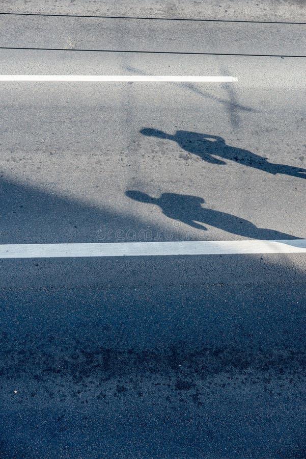 Sombras dos corredores na estrada fotografia de stock royalty free