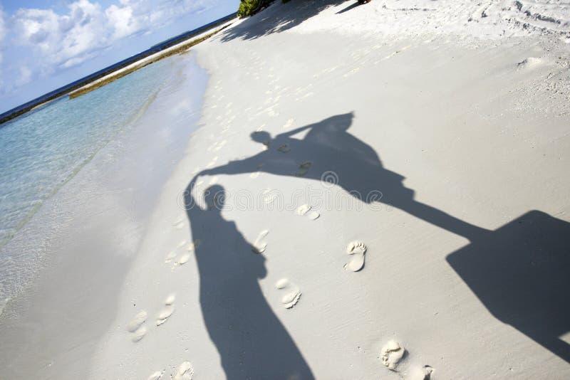 Sombras dos povos em areias da praia fotografia de stock