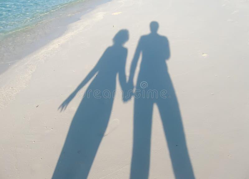 Sombras en la arena de la mujer y del hombre que llevan a cabo las manos foto de archivo libre de regalías