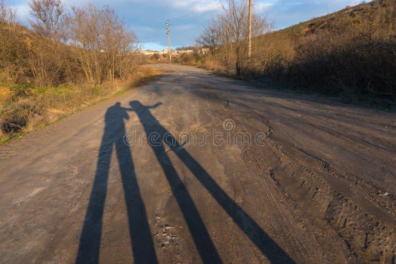 Sombras longas dos pares na estrada de terra no por do sol imagens de stock