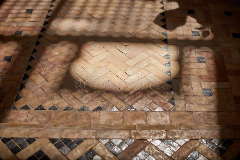 Sombras no assoalho de mosaico de pedra tradicional de Morrocan dentro do Riad fotos de stock