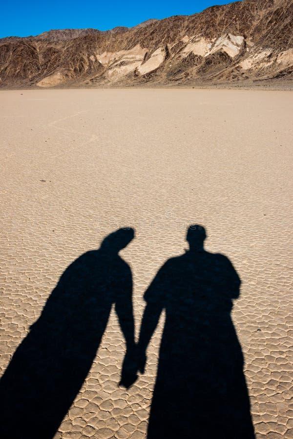 Sombras que llevan a cabo las manos en el desierto fotos de archivo libres de regalías