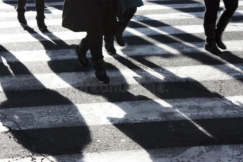 Sombras y siluetas de la gente que cruza la calle imagen de archivo