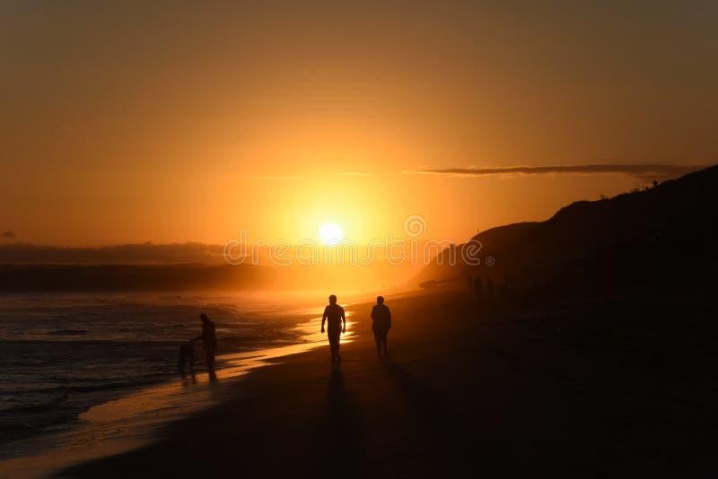 Sombras y siluetas en la playa antes de la puesta del sol imagenes de archivo