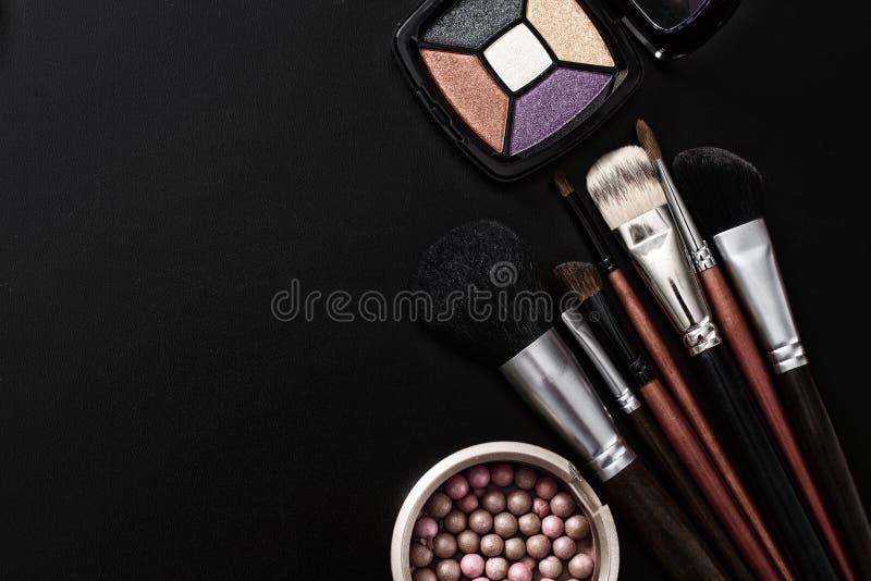 Sombreadores de ojos, cepillos del maquillaje Los productos cosméticos en fondo negro y componen las herramientas Visión superior imagen de archivo