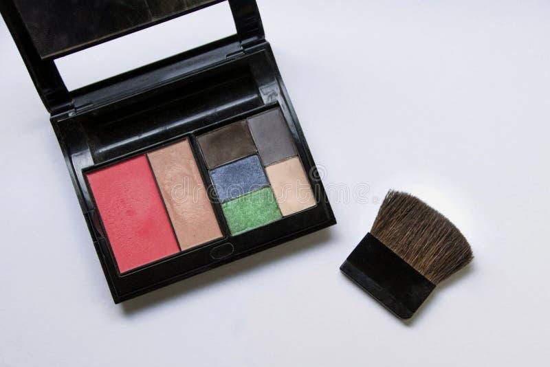 Sombreadores de ojos y cepillo y cosm?ticos del maquillaje, en un fondo blanco, fotografía de archivo libre de regalías