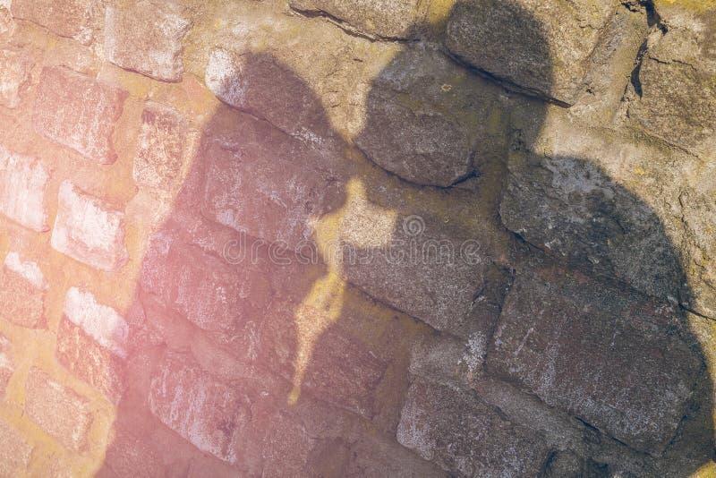 Sombree la silueta de pares hermosos en beso en la pared de piedra fotografía de archivo