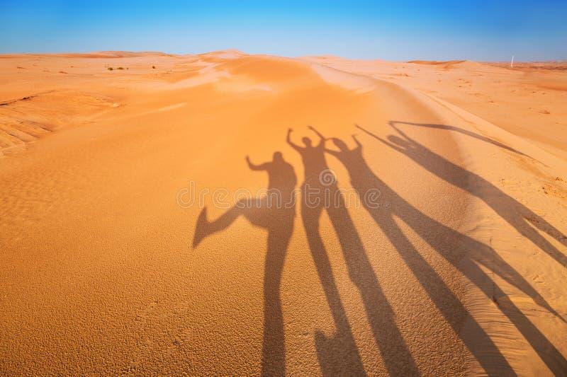 Sombree las siluetas de cuatro personas en el desierto imagenes de archivo
