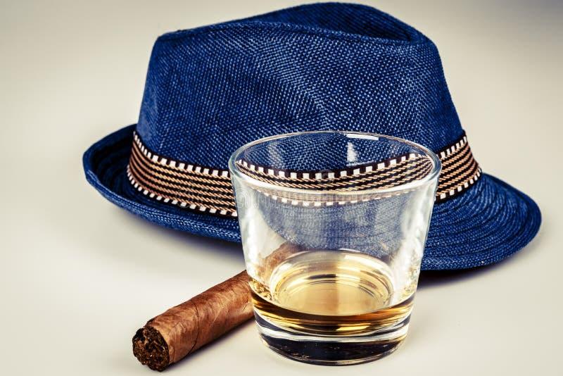 Sombrero azul con el cigarro y la bebida costosa del whisky o del ron en el piso blanco fotografía de archivo libre de regalías