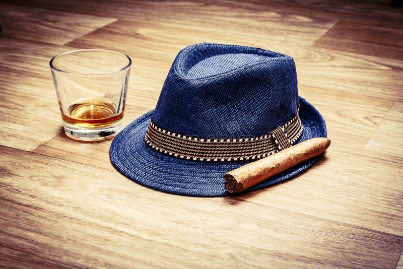 Sombrero azul con el cigarro y la bebida costosa del whisky o del ron en piso de madera imágenes de archivo libres de regalías