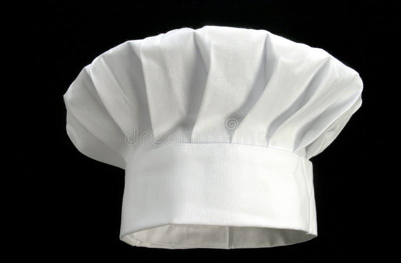 Sombrero blanco doblado del ` s del cocinero en un fondo negro foto de archivo