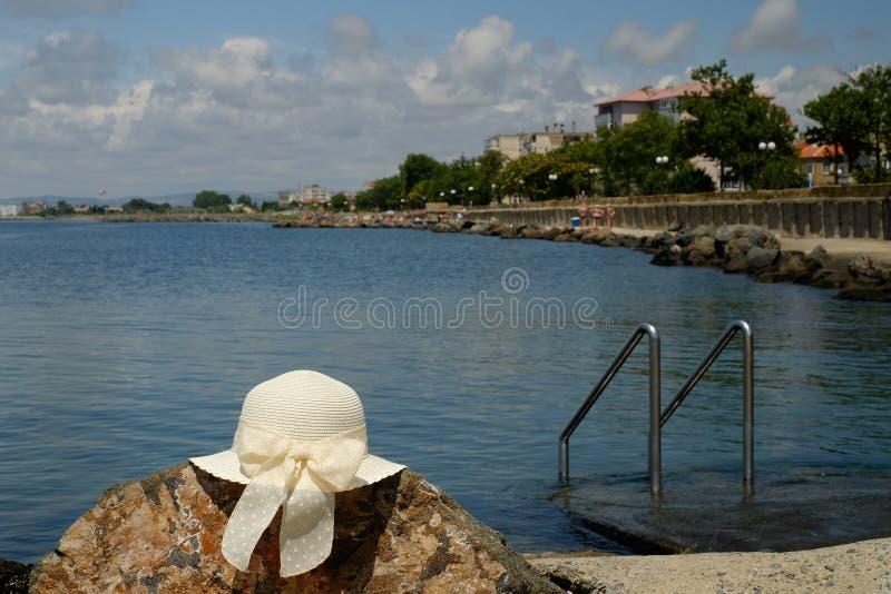 Sombrero blanco en las rocas cerca del embarcadero del mar con la vista del agua fotos de archivo libres de regalías