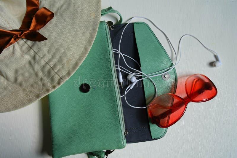 Sombrero, bolso, auriculares, vidrios en el fondo blanco imagen de archivo libre de regalías