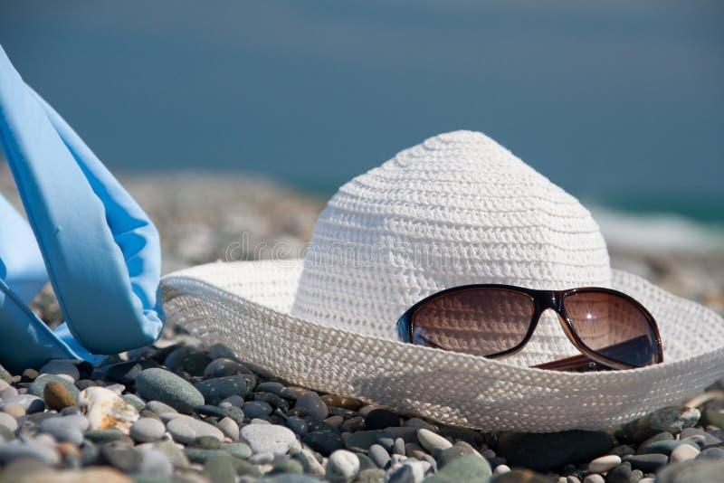 Sombrero, bolso, y vidrios en la playa fotografía de archivo