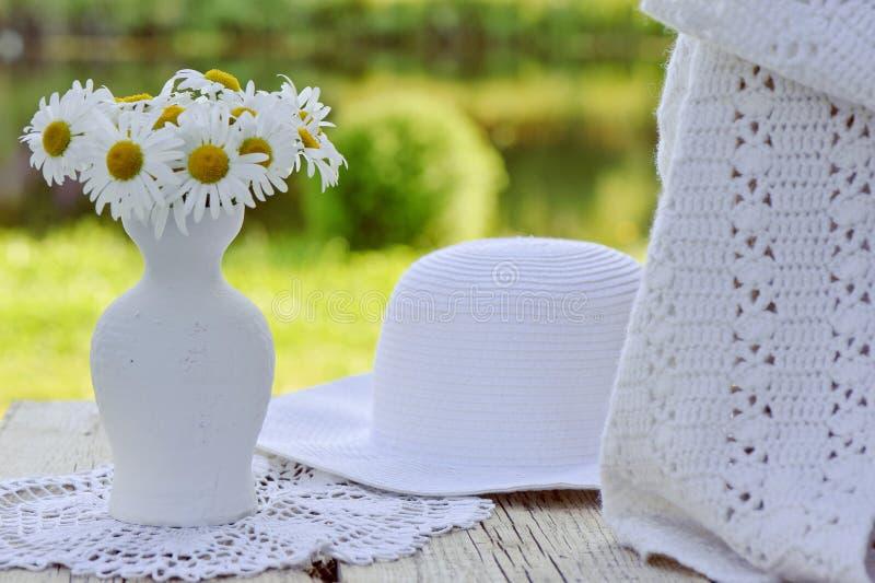 Sombrero, bufanda y ramo blancos de manzanilla en florero imagen de archivo