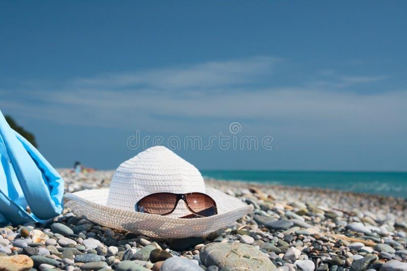 Sombrero con las gafas de sol en los guijarros imagen de archivo libre de regalías