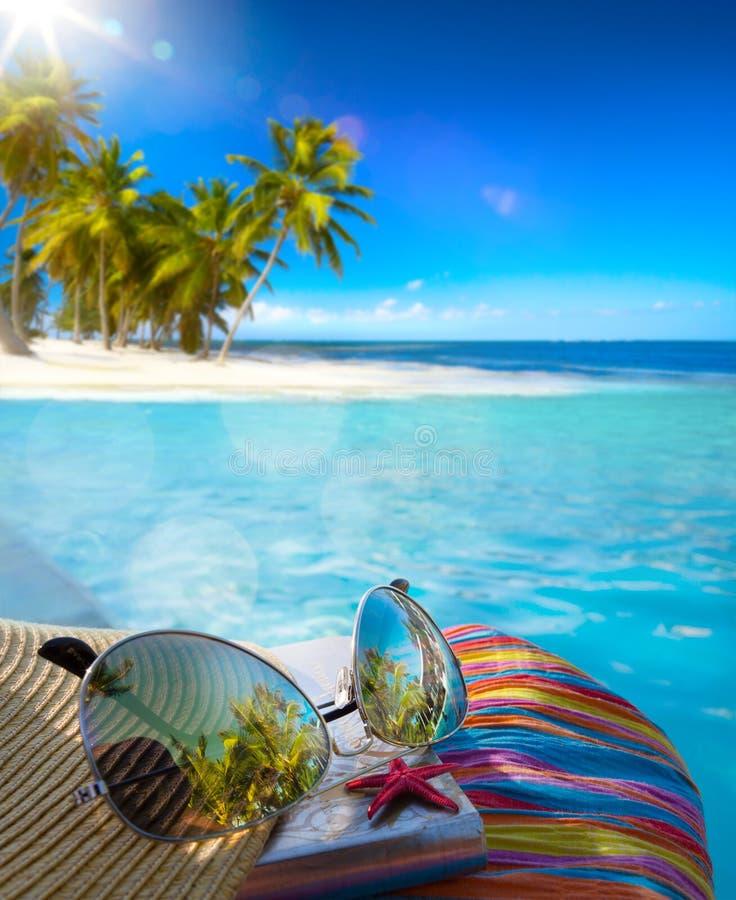 Sombrero de Art Straw, bolso y vidrios de sol en una playa tropical foto de archivo libre de regalías