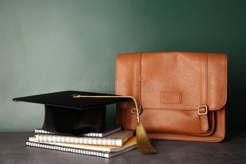 Sombrero de la graduación con los cuadernos y la cartera imagen de archivo
