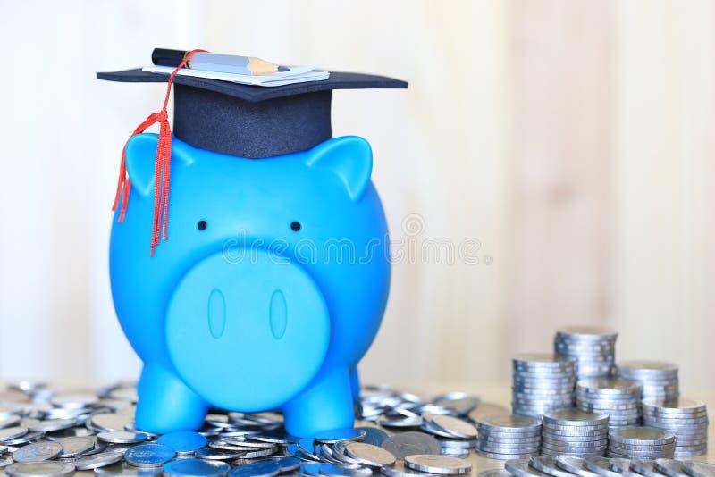 Sombrero de la graduación en la hucha azul con la pila de dinero de las monedas en el fondo de madera, dinero de ahorro para el c fotos de archivo