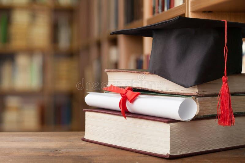 Sombrero de la graduación en la pila de libros y de diploma imagen de archivo